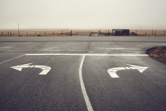 Left or right, roads intersection on a rainy day, color toning applied, Wyoming, USA.