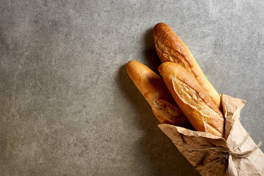 Fresh french baguettes packed in paper on a gray stone surface. Top view.