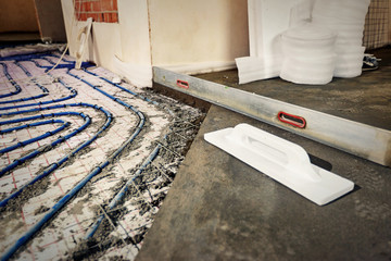 Laying blue pipes for floor heating at the construction site.