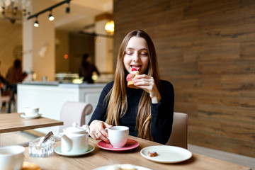Young woman sits with cafe and enjoys a delicious dessert