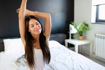 Cheerful young woman sitting in bed and stretching. What a great morning.
