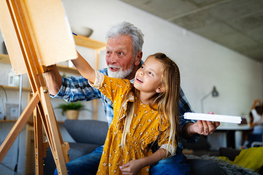 Senior man with child painting on canvas. Grandfather spending happy time with granddaughter.