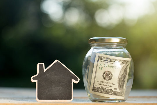 Real estate concept - money jar and little house with space for text on the wooden table in the garden