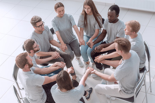 young people holding each other's hands at a group meeting.