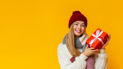 Cheerful winter girl with new year gift