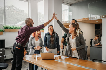 Diverse business team celebrating and giving high fives during boardroom meeting