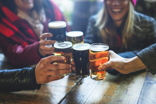 Group of happy friends drinking and toasting beer at brewery bar restaurant - Friendship concept with young people having fun together at cool vintage pub - Focus on right pint glass - High iso image