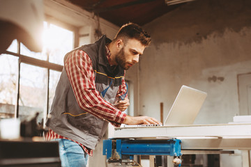Young man work in home workshop using laptop and reads the manual