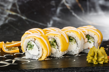 Aluminium Prints Sushi bar Sushi Rolls with processed cheese, cheddar, american cheese, avocado, mango and Cream Cheese inside on black slate isolated on black marble background. sushi with mango. Sushi menu. Horizontal.