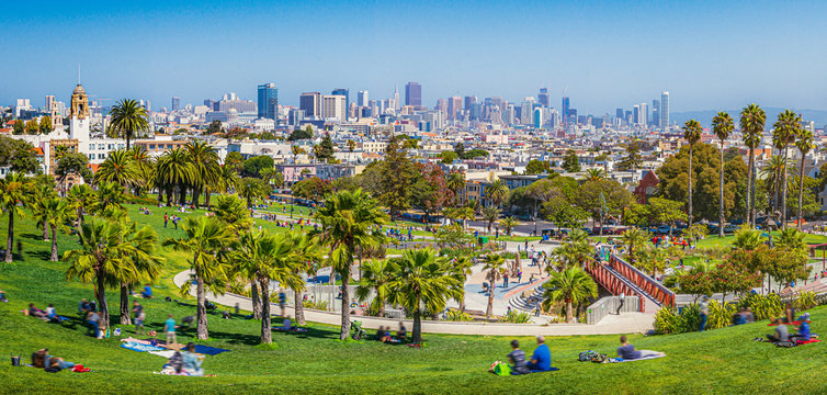 Panoramic view of local people enjoying the sunny summer weather at Mission Dolores Park on a beautiful day with clear blue sky with the skyline of San Francisco in the background, California, USA