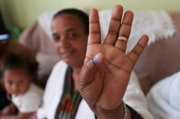 Yerusalem Kawiso, 48, a government employee who lost a brother, brother in law and a great uncle to Sidama struggle, shows her inked finger after voting for the Sidama autonomy during the referendum vote in Hawassa