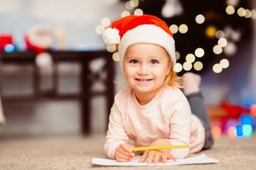 Little girl writing wishlist, lying on floor near Christmas tree