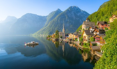 Foto auf Leinwand Schiff Classic panoramic view of famous old town Hallstatt and alpine deep blue lake with tourist ship in scenic golden morning light on a beautiful sunny day at sunrise in summer, Salzkammergut, Austria