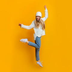Cheerful blonde girl dancing and jumping in the air