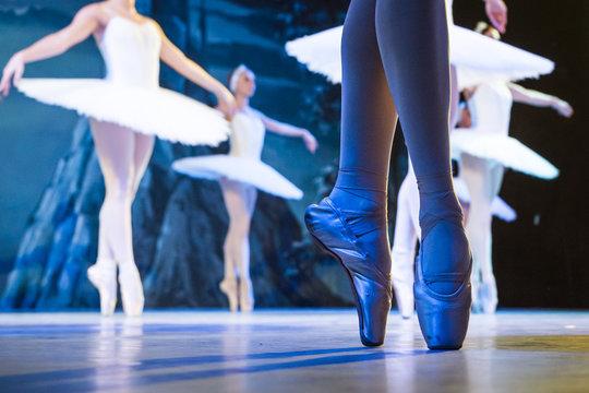 Legs of ballerinas dancing in ballet Swan Lake.