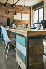Empty industrial style office with wooden chest of drawers in the foreground