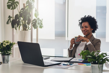 Happy smiling african-american business woman working on laptop at office. Businesswoman sitting at her working place