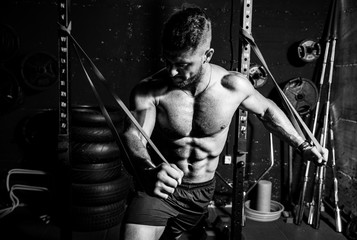 Young sweaty strong focused fit muscular man chest stretching cross workout training in improvised gym with rubber for strength and good looking of muscles dark image black and white