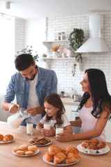 husband pouring milk from the jug into the glasses for wife and daughter in the kitchen