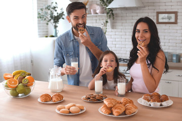 portrait of happy family eating cookies with milk and looking at the camera