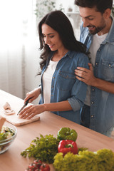 woman slicing mushrooms on the cutting board while man hugging her from the back on the kitchen