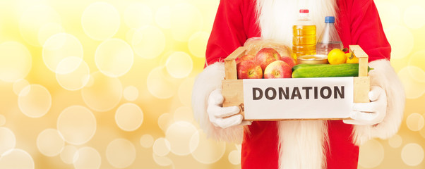 Santa Claus and a box with food. Christmas donation concept.