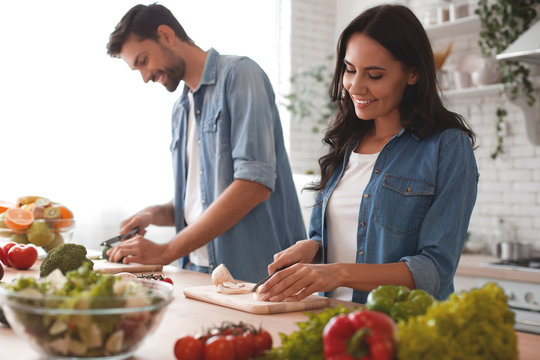 smiling wife and husband cooking dinner in the kitchen together