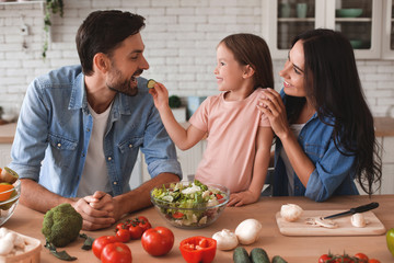 family preparing salad for lunch, daughter feeding father with slice of cucumber on the kitchen