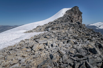 Hiker nearing the summit of mountain giant in Jotunheimen Norway