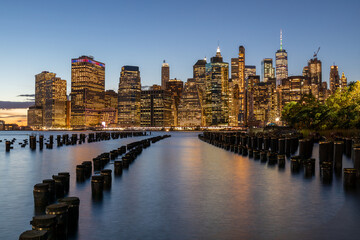 NYC Cityscape in Sunset Light. Old Pier in Foreground. Lower Manhattan Cityscape in Background. Skyscraper