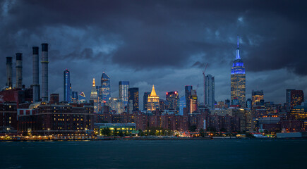 NYC Cityscape with Stormy Cloudy Blue Sky in Background. The Smoke Stacks on the left in the background.