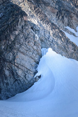 Snow wall against the rocky mountainside natral shape and lines Norway