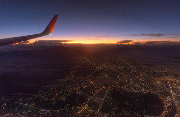 View from a landing airplane out the window of city at sunset