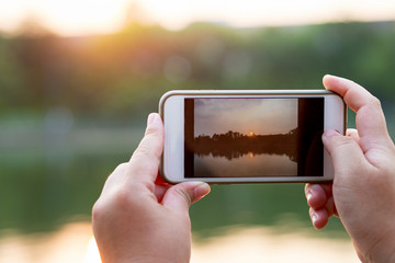 Hands holding smart phone taking photo of evening sunset landscape