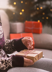 Woman unpacking Christmas gift over background with tree