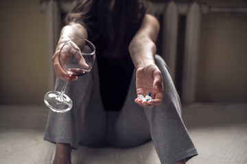 Photo sur Plexiglas Bar a young girl sitting in a dirty room, with a glass of wine, and holds pills in her hand. Poisoning when mixing alcohol and drugs. Polydrug addiction in women