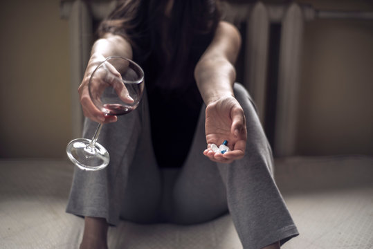 a young girl sitting in a dirty room, with a glass of wine, and holds pills in her hand. Poisoning when mixing alcohol and drugs. Polydrug addiction in women