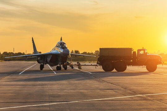 Military fighter is being pushed to a parking lot by a military vehicle at an air base in the evening at sunset.