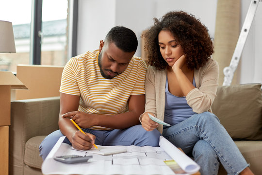 mortgage, moving and real estate concept - sad african american couple with blueprint and calculator counting money for repair costs to new home