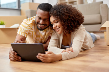 mortgage, people and real estate concept - happy african american couple with tablet pc computer lying on floor at new home