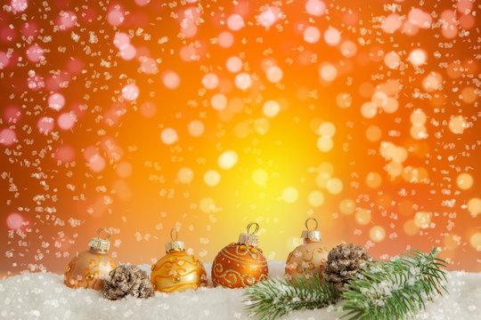 Goldene Christbaumkugeln liegen im Schnee vor einem orangefarbenem Hintergrund mit bokeh