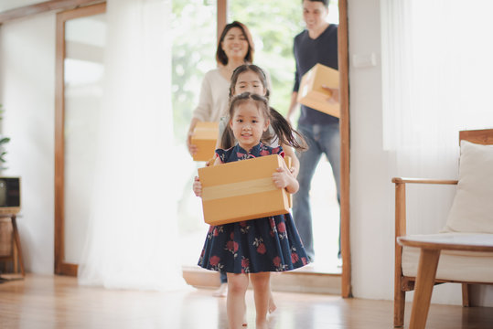 Young Asian family with daughter holds carton and walking in to a new home in moving relocation day which Excited smiling and felling happy. Mother Father and daughter move on a new home concept.