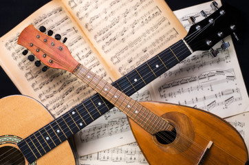 Mandolin and guitar with blurred sheet music books on a black background. Stringed musical instruments.