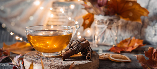 Cozy autumn or winter at home. A cup of tea, autumn casts a book a garland on a wooden table near a...