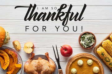 top view of roasted turkey, pumpkin pie and grilled corn served on white wooden table with i am so...