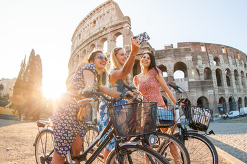 Three happy young women friends tourists with bikes taking selfies at Colosseum in Rome, Italy at sunrise.