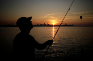 A fisherman holds his rod as the skyline of Beirut is seen in the background during sunset from Antelias