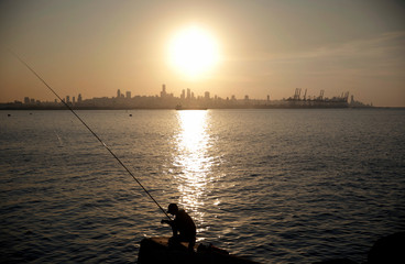 A boy fishes from a breakwater as the skyline of Beirut is seen in the background during sunset in Antelias