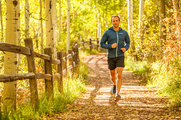 Telluride, Colorado, USA: A male runner jogging along a trail on a sunny autumn day.