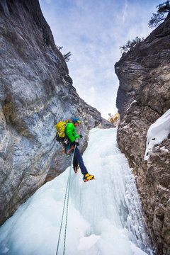 A man  rapells down a icy gully after climbing  Rainbow Serpent (100m WI6) in the Recital Hall, a beautiful rock ampitheatre in the Ghosts in Alberta, Canada. The approach to get to Rainbow Serpent involves climbing numerous moderate pitches of ice that are rapelled down during the descent.